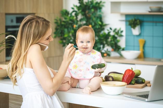 スプーンで女の赤ちゃんを授乳する母親。母は家で彼女の愛らしい子供に食べ物を与えます。ベビーフード。在宅勤務。電話を使用して。