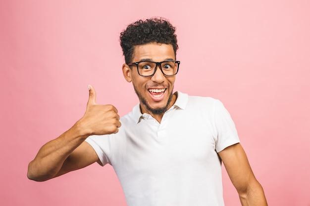 親指を現してピンクの背景に対して隔離されるカジュアルに身を包んだ陽気な笑顔の若いアフロアメリカンの男の肖像。