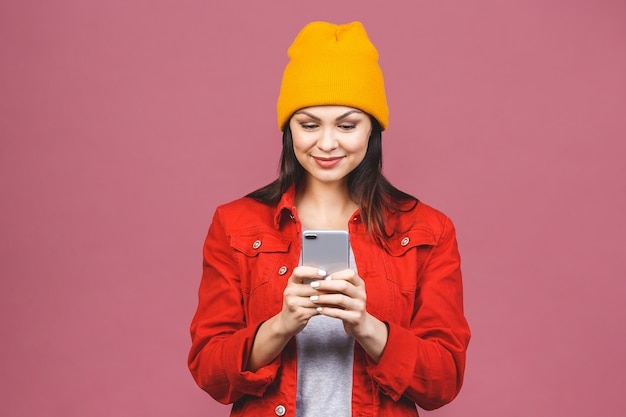 Фото жизнерадостной милой красивой молодой женщины беседуя мобильным телефоном изолированным над розовой стеной стены.