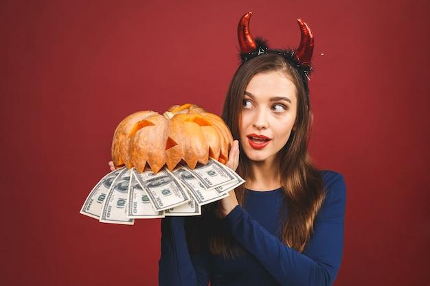 Хэллоуин ведьмы с резными тыквы и деньги - изолированные на красном фоне. эмоциональная молодая женщина в костюме хэллоуина.