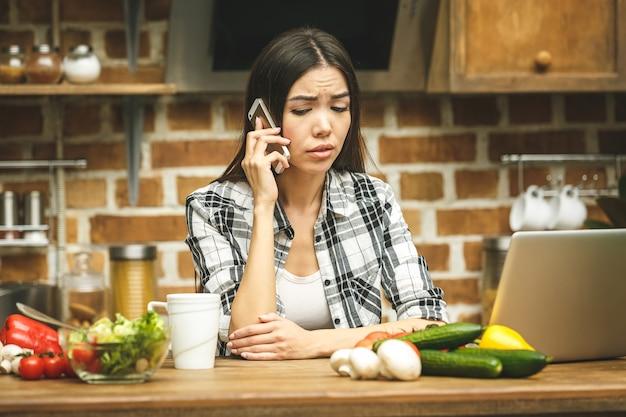 Молодая красивая азиатская усиленная женщина с компьтер-книжкой на кухне. с помощью телефона. работаю дома. в стрессе.