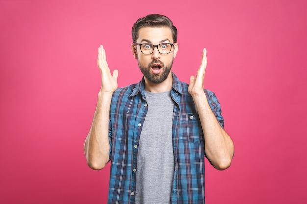 ピンクの背景に立っている間カメラを見てメガネでハンサムな若い男。ひげを生やした男の口を開いたままにするポートレートを閉じます。