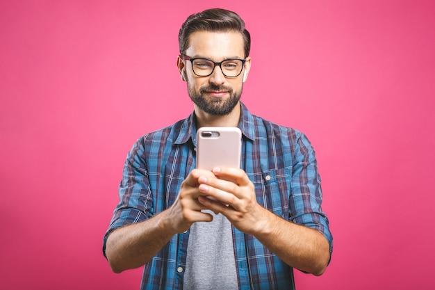 スマートフォンを押しながらそれを見て笑顔の若い男。携帯電話を使用して幸せな男の肖像