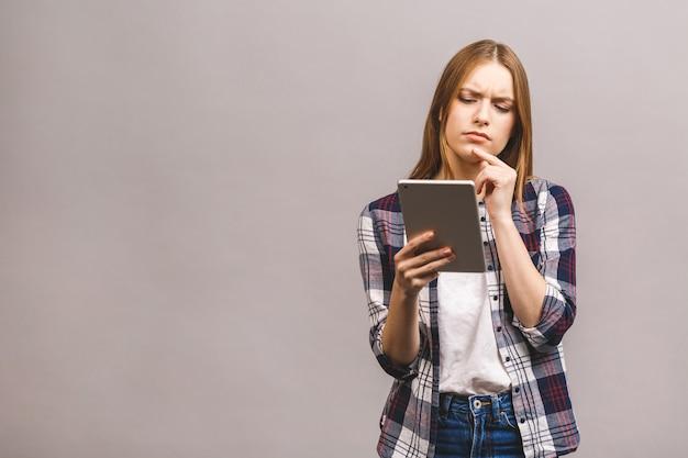 Серьезное мышление красивая молодая женщина в случайных с использованием цифрового планшета.