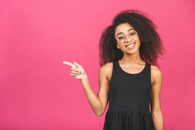 ピンク以上のコピースペースで指を指して幸せな若い女の肖像画。