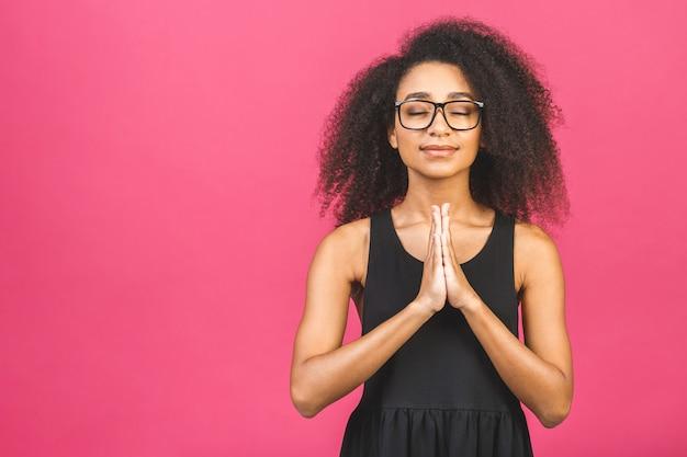 瞑想のコンセプトです。美しい若い女性は瞑想的なポーズで立って、平和な雰囲気を楽しんで、ピンクの上で祈りのジェスチャーで手をつないでいます。
