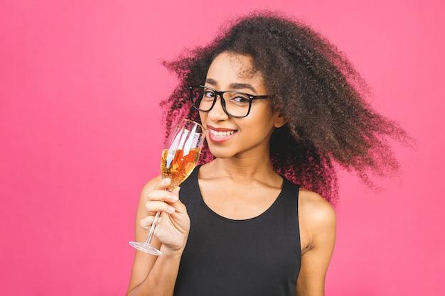 С днем рожденья! портрет счастливой афро-американской негритянки с бокалом шампанского на розовый.