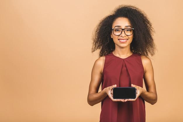 ベージュで空白の画面の携帯電話を保持している笑顔の若い女性の肖像画。