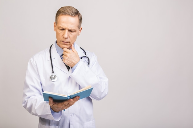 Старший доктор читая книгу изолированную над серой стеной.