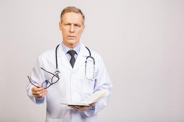 Старший доктор держа книгу изолированный над серой стеной.