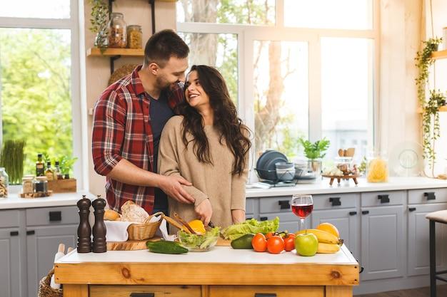 Красивая молодая усмехаясь счастливая пара говорит и усмехается пока варящ здоровую еду в кухне дома.