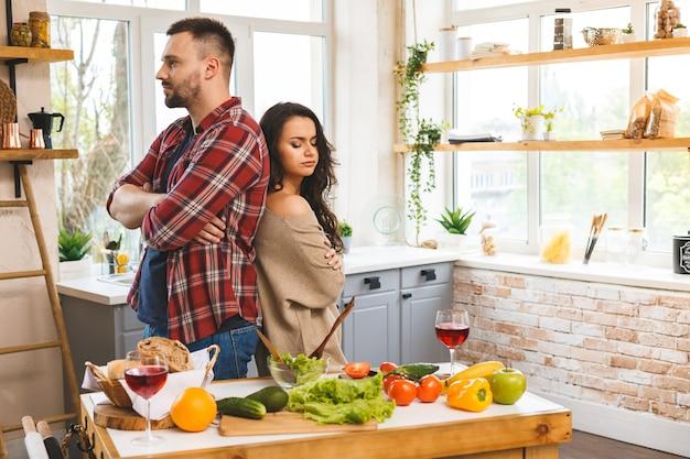 けんかを持っているカップル。キッチンに立っている男性と女性が叱る