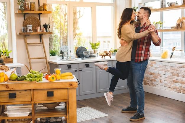 キッチンで踊る。婚約コピースペースを祝うロマンチックなカップル。家で踊るかわいい若いカップル。