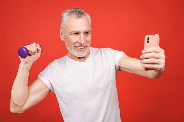 Время селфи! портрет конца-вверх старшего человека работая с гантелями. с помощью телефона.