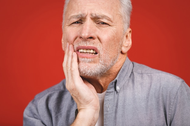 歯痛に苦しんでいる年配の男性。