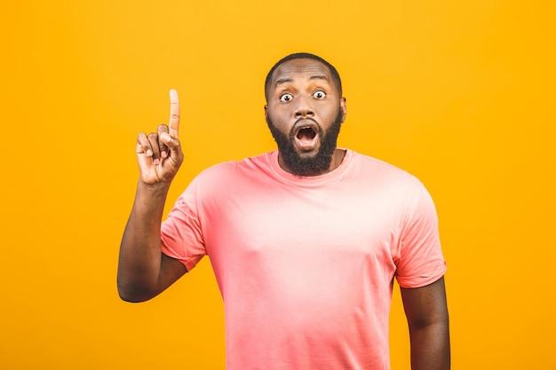 Портрет счастливого молодого симпатичного афроамериканского человека с в случайной улыбке, указывая в сторону пальцем