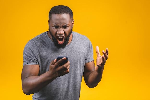 Молодой афроамериканец человек с помощью смартфона подчеркнул, шокирован лицом стыда и удивления, злой и разочарован. страх и расстроен за ошибку.