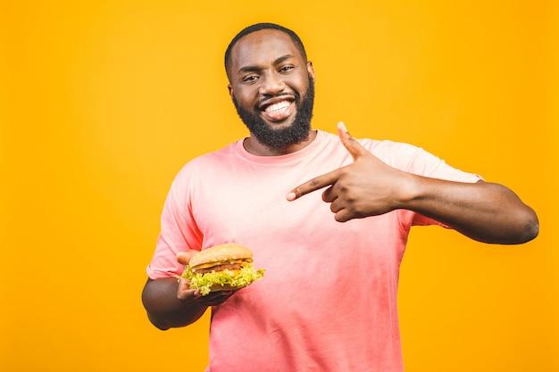 黄色の壁に分離されたハンバーガーを食べる若いアフリカ系アメリカ人。