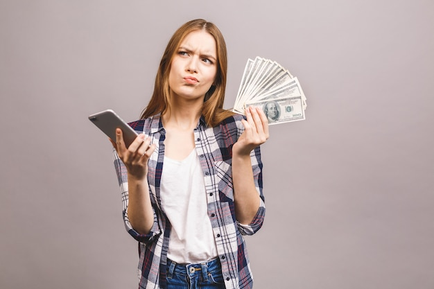 興奮した若い女性のイメージ。お金を持って携帯電話に驚いた。