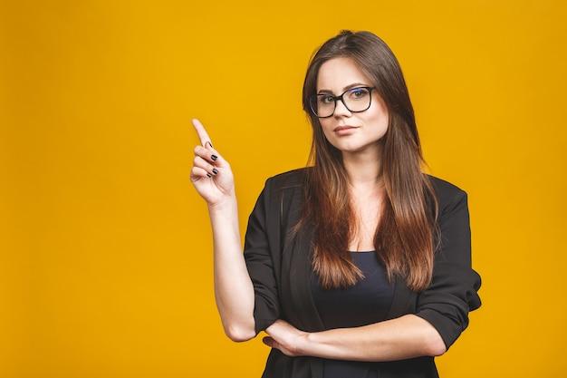 Портрет улыбающиеся молодые деловая женщина, указывая и глядя
