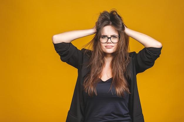 ストレスの概念。彼女の髪を引っ張って非常にイライラして怒っているビジネスウーマン。黄色に対して隔離されます。