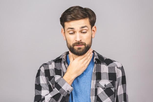 喉の痛み。灰色の灰色の白い壁に対して隔離される首に触れる男性。