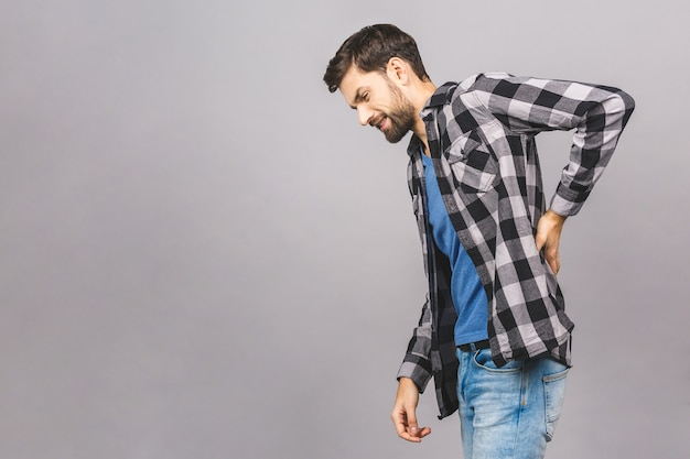 灰色の灰色の壁のコピースペースに分離されたカジュアルな身に着けている背中の男の深刻な痛みに不満をゆがめる悲しい動揺の肖像画。