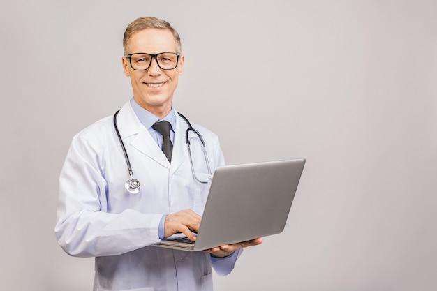 灰色の背景に分離されたラップトップを使用して上級成熟した医師の肖像画。