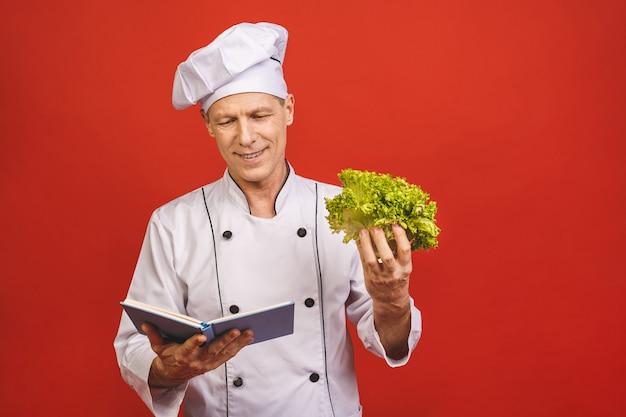 Портрет счастливого старшего мужского шеф-повара держа книгу рецепта и подготавливая еду изолированную на красной предпосылке.