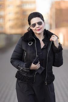 Брюнетка в коричневой куртке и солнцезащитных очках