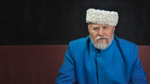 Крупным планом портрет старшего мужчины с бородой, глядя в камеру