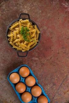 卵のカートンが付いているパセリが付いているフジッリのねじで調理されていないパスタ