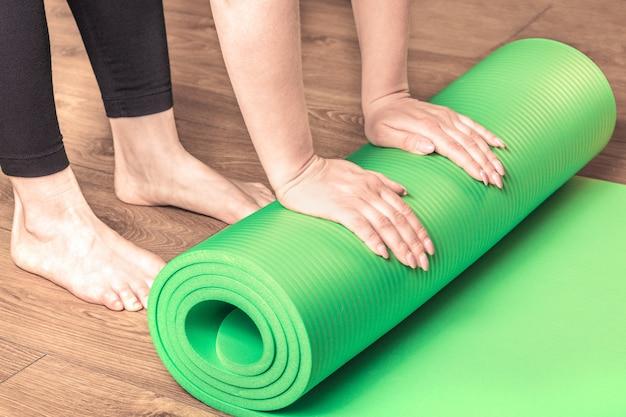 トレーニング後にヨガマットを転がしている女性。木の床。コンセプト健康的なライフスタイル。