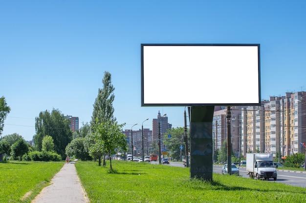 道路に沿って立っている空または空白の広告看板。モックアップ