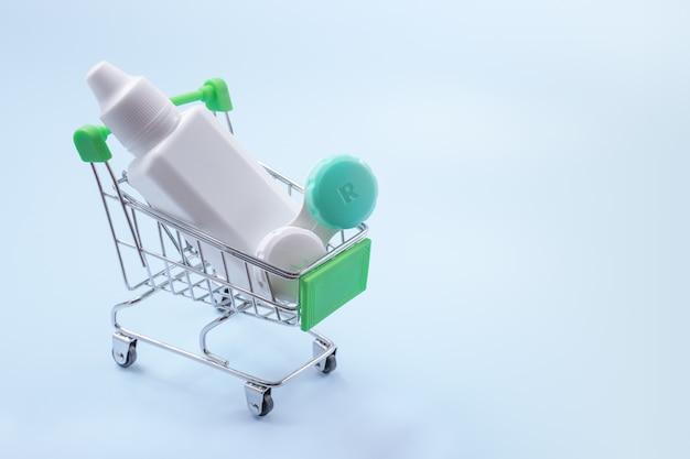 Контактные линзы и линзы жидкие в продуктовой корзине. концепция покупок контактных линз.