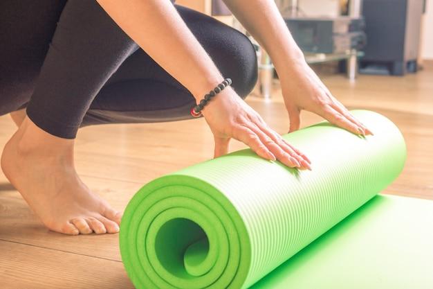 Женщина катает ее коврик для йоги дома после тренировки на деревянном полу