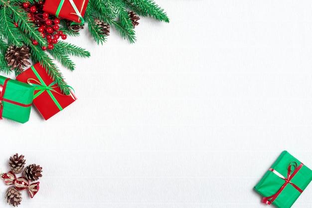 モミの枝、お祝いデコレーション、ギフトボックス、赤いヒイラギの果実、白いテーブルの上の松ぼっくりで作られたクリスマスフレーム。