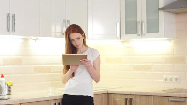 Портрет счастливой копирайтер женщина работает независимый проект онлайн, сидя у себя дома на кухне
