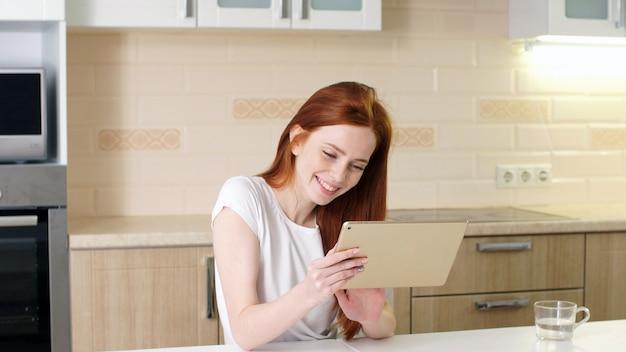 Красивая девушка с помощью планшета и интернета, покупки онлайн, заказ еды, бронирование билетов, сидение дома