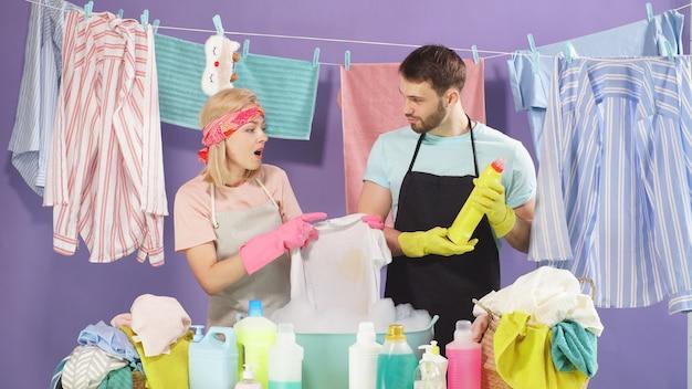 可愛い夫婦がしみや汚れのある汚れた服を洗うのに洗剤を選びました