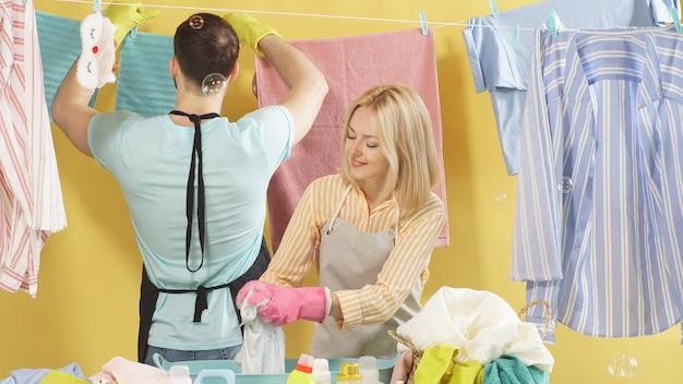 陽気な笑顔の勤勉なカップルは、手洗いにおすすめの服を洗います。洗面器で服を洗う