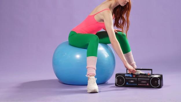 ジムでピラティストレーニングをしている赤い髪の少女