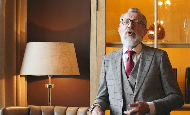 Успешный, зрелый, модный пенсионер, старик в очках и костюме сидит в кожаном кресле в своем кабинете