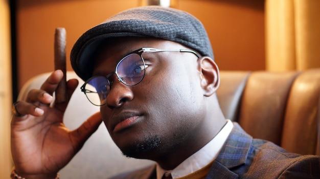 彼の眼鏡の後ろから陰気なアフリカ系アメリカ人の視線のクローズアップ。黒人男性のクローズアップの肖像画