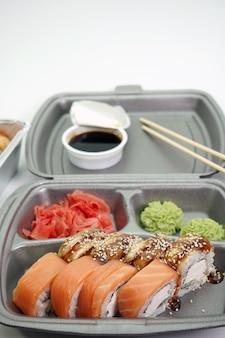 ロール寿司は、孤立した壁にプラスチック包装のクローズアップで梱包されています