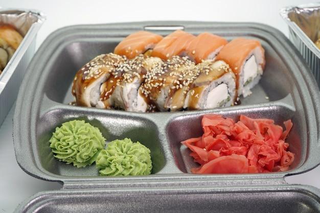 食品配達と巻き寿司のクローズアップ。フードデリバリーのコンセプト