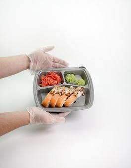 孤立した白い壁に各種の巻き寿司。日本料理のお届け