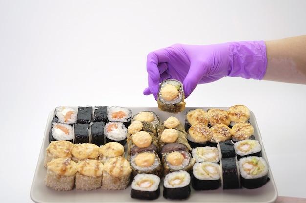 プレート、孤立した壁にロール寿司をレイアウト女性の手袋をはめた手のクローズアップ