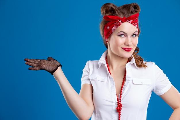 Милая улыбающаяся женщина в стиле пин-ап, указывающая на место для вашей рекламы