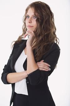 Красивая деловая женщина в строгом костюме задумчиво смотрит в сторону от чего-то